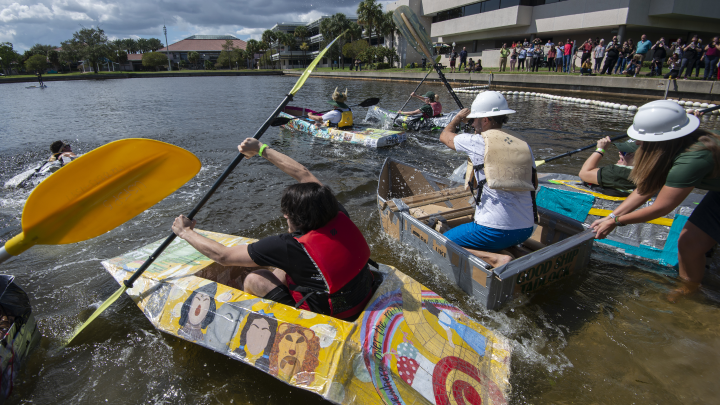 several people in cardboard boats with others looking on in the background