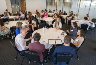 Students and business leaders sitting at round tables in a conference room