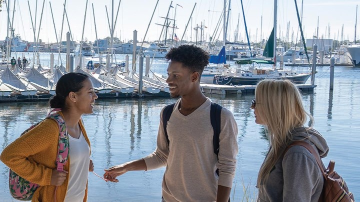 three students talking with boats in the background