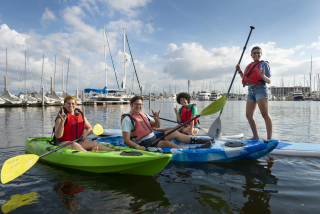 students in kayaks and paddleboards