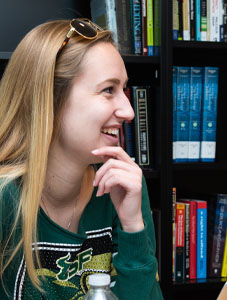 woman student smiling in library setting