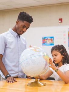 male student teacher looking at globe with young girl