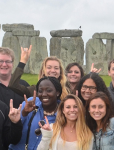 group of students smiling with stonehenge in background