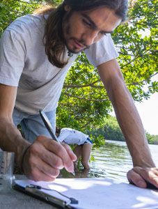 male student writing notes while researching in water