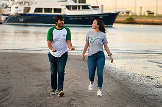 young man and woman walking on beach are near campus