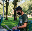 student on bench on campus wearing mask and working on laptop