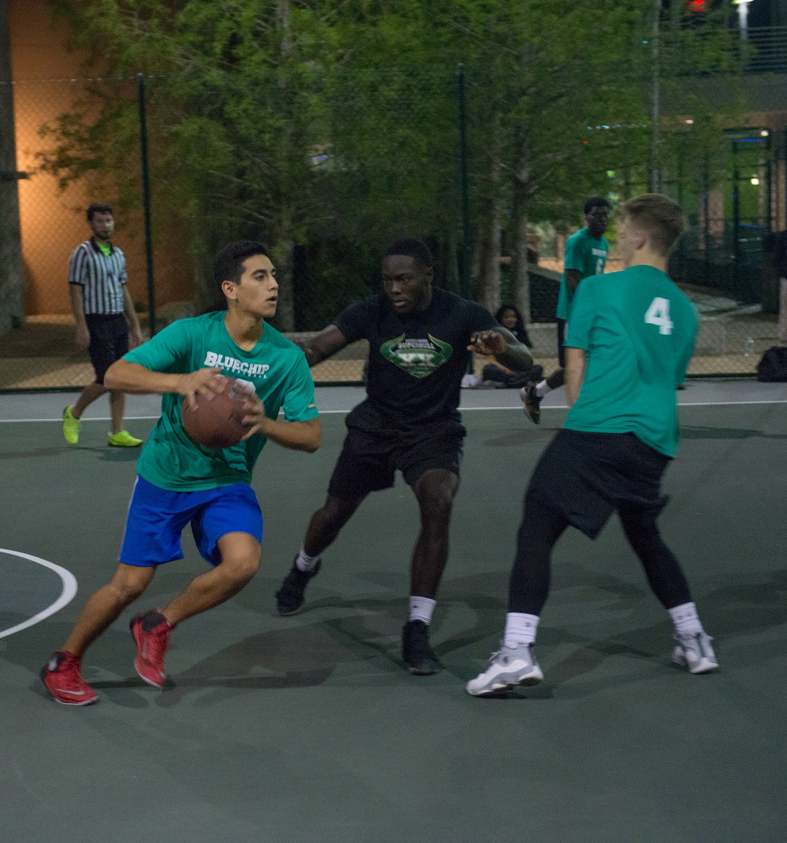 three students playing basketball