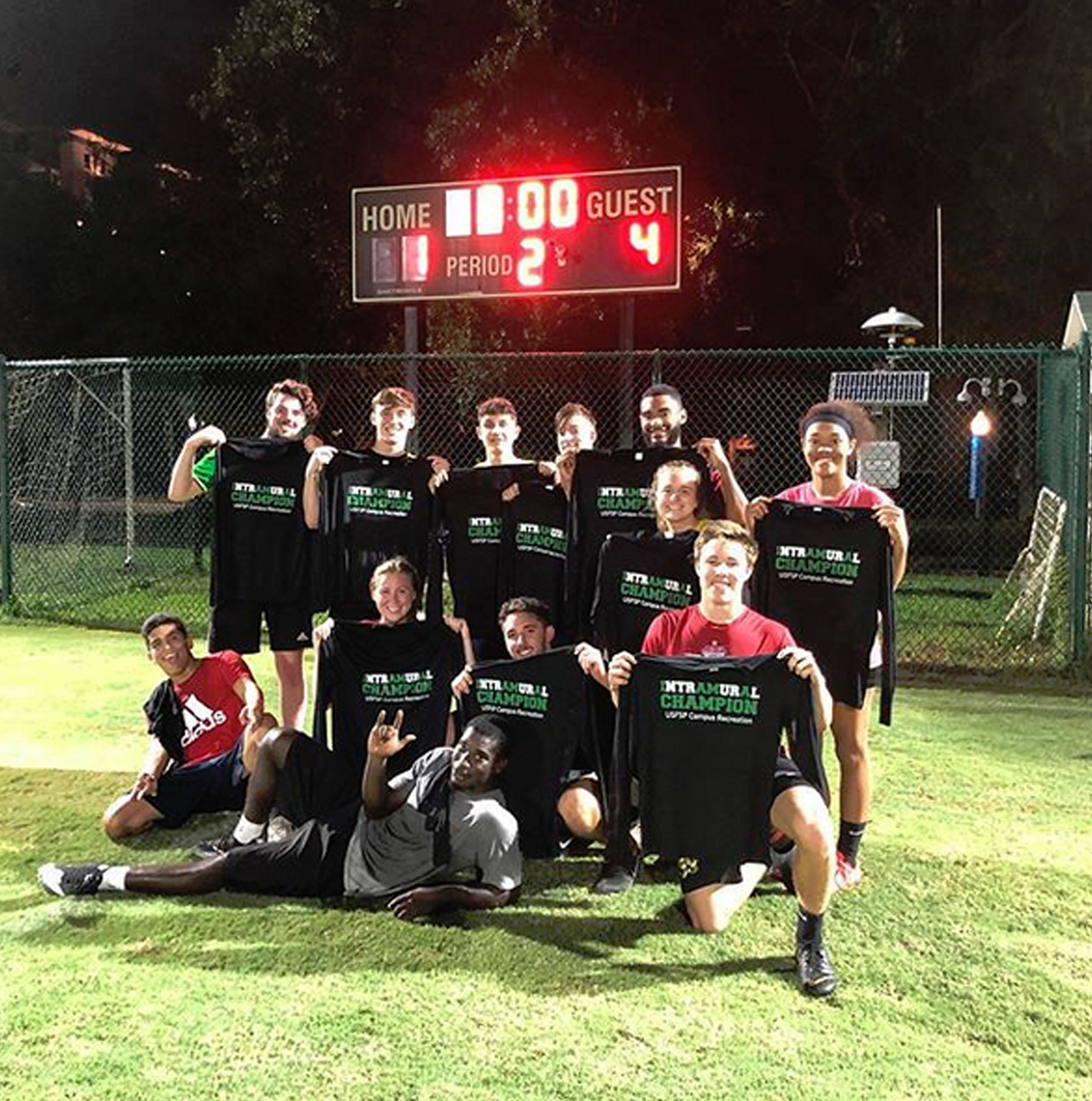 Intramural team poses with victory t-shirts on soccer field